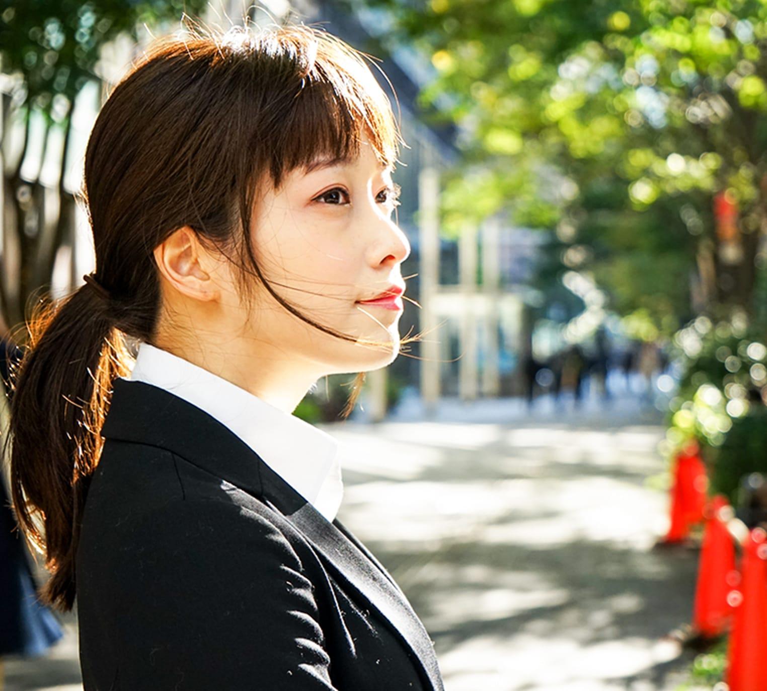 遠くを見つめるスーツ姿の若い女性の画像